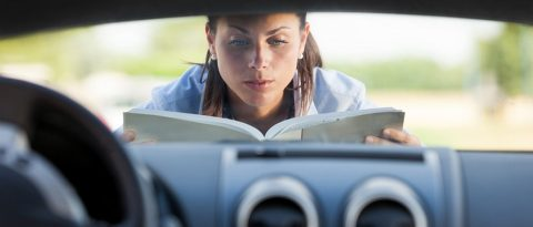 Woman reading manual on hood of new car