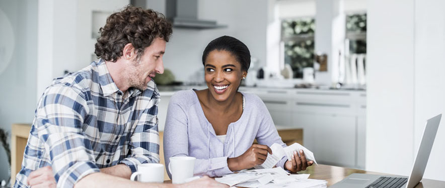 Couple looking through receipts inside their kitchen table